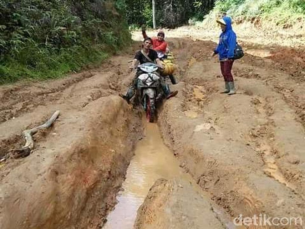 Warga membantu mengangkut material bangunan menggunakan sepeda motor dengan melewati jalan yang curam dan licin.