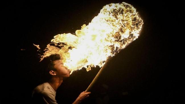 Di Desa Cibiru Hilir, Cileunyi, Bandung, Jawa Barat, seorang warga melakukan atraksi dengan menyemburkan bahan bakar ke api saat pawai obor.(Antara/Raisan Al Farisi)
