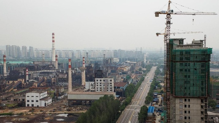 abrik Baja dan Besi Guofeng yang telah dinonaktifkan dan sebuah gedung apartemen yang sedang dibangun di Tangshan, provinsi Hebei, China, August 22, 2018. Picture taken August 22, 2018.  REUTERS/Thomas Peter