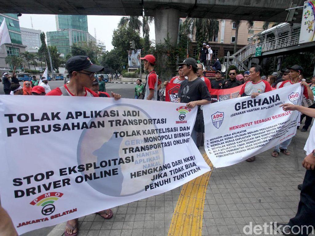 Massa berdemo di bagian belakang gedung Pasaraya Blok M di Jalan Iskandarsyah II. Massa membawa berbagai atribut demonstrasi seperti bendera dan spanduk.