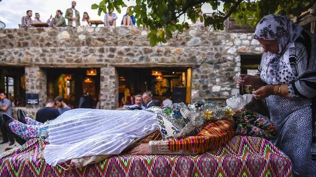 Riasan ini dibuat dengan tujuan tertentu. Para wanita yang sudah dewasa merias para calon pengantin dengan riasan berlapis dan beragam motif. (AFP PHOTO / Armend NIMANI)