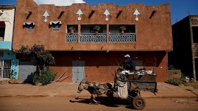 Dari pintu ke pintu, mereka mengambil sampah yang kemudian diangkutnya menuju pengepul sampah lokal. (REUTERS/Luc Gnago)