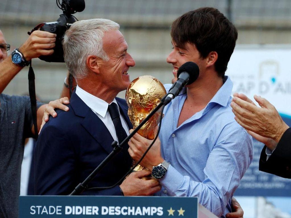 Di dalam seremoni itu, Deschamps dikejutkan dengan kunjungan putranya, Dylan. Dylan menyerahkan trofi juara Piala Dunia, yang dimenangi Prancis di Rusia lalu. (Foto: Eric Gaillard/Reuters)