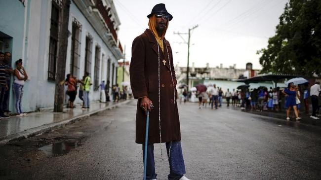 Seorang tukang bangunan bernama Francisco Valdez sedang menanti prosesi Virgin of Regla di area pantai Regla, sebuah distrik di pelabuhan Havana, Kuba. (REUTERS/Alexandre Meneghini)