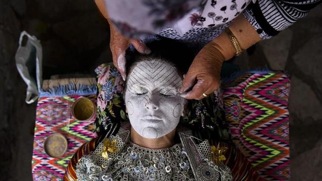 Kosovar Sheqerie Buqaj tengah berbaring sembari seorang wanita yang dituakan merias wajahnya. Buqaj memutuskan menikah dengan riasan tradisional Bonsia. (AFP PHOTO / Armend NIMANI)