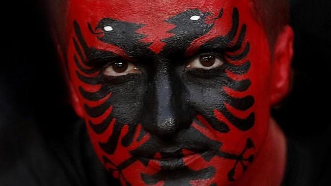 Seorang penggemar timnas Albania dicat wajahnya kala mendukung kesebelasan tersebut di laga melawan Skotlandia di Glasgow. (REUTERS/Russell Cheyne)