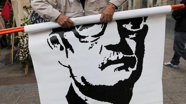 Seorang pria menggulung gambar wajah mendiang presiden Chile, Salvador Allende, saat peringatan 45 tahun kudeta militer 1973 di Santiago, Chili. (REUTERS/Ivan Alvarado)