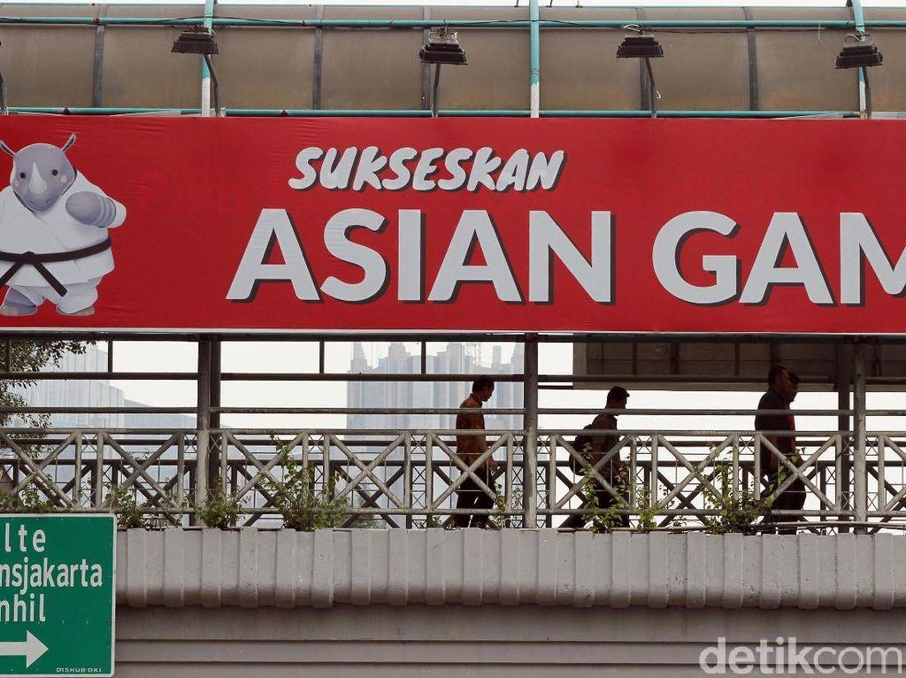 Warga melintasi JPO yang terdapat spanduk promosi Asian Games di kawasan Benhil, Jakarta Pusat.