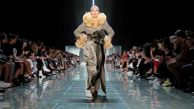 Ikatan rosette berukuran besar pada celana panjang satin, gaun tartan dengan banyak lapisan, dan tak lupa permainan ruffles yang dihadirkan membuat busana yang dipamerkan itu seolah 'meledak'. (REUTERS/Andrew Kelly)