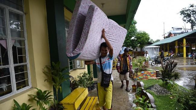 Keluarga di Cagayan mengangkut semua barang dari dalam rumahnya agar tidak terkena banjir yang akan dibawa Topan Mangkhut ketika tiba di wilayah itu pada Sabtu (22/9) pagi. (AFP Photo/Ted Aljibe)