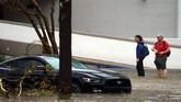 Orang-orang berusaha melewati banjir yang mampir di kota mereka, Wilmington. Banjir itu datang dibawa oleh Badai Florence yang menerpa sebagian kota di Carolina Utara. (REUTERS/Carlo Allegri)