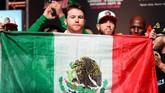 Canelo Alvarez mengibarkan bendera Meksiko sebelum melakukan timbang badan. Canelo untuk kali kedua akan menghadapi Gennady Golovkin dalam perebutan gelar juara dunia kelas menengah WBA Super, WBC, IBO, dan The Ring. (REUTERS/Joe Camporeale-USA TODAY Sports)
