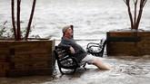 Seorang pria duduk di bangku taman yang dipenuhi air banjir. Badai Florence membuat air sungai Cape Fear di Wilmington meluap hingga ke taman-taman. (REUTERS/Jonathan Drake)