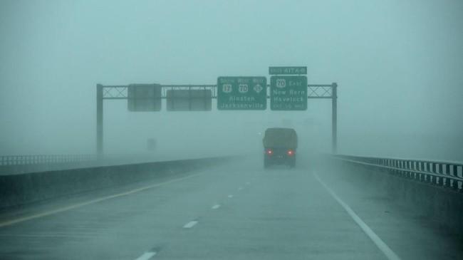 Angin kencang dan hujan deras membuat jarak pandang memendek ketika truk penyelamat menyebrang jembatan di sungai Neuse, New Bern, Carolina Utara. (Chip Somodevilla/Getty Images/AFP)