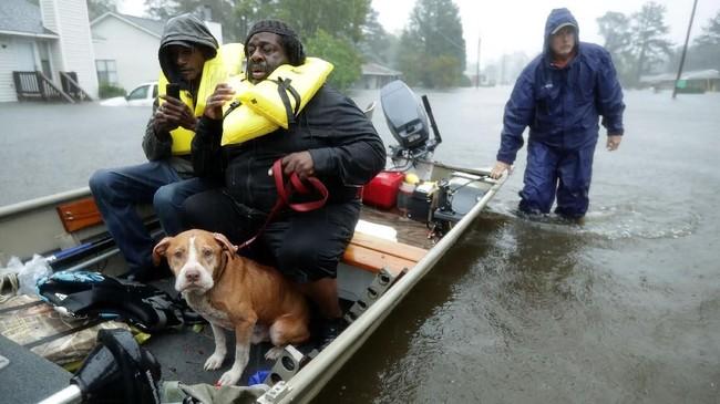 Para relawan dari Carolina Utara membantu menyelamatkan penduduk serta hewan peliharaan mereka untuk mengungsi ketika terjadinya banjir akibat Badai Florence. (Chip Somodevilla/Getty Images/AFP)