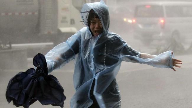 Seorang wanita berusaha menyeimbangkan tubuhnya saat diterpa Topan Mangkhut di Shenzhen, China pada September 16, 2018. (REUTERS/Jason Lee)