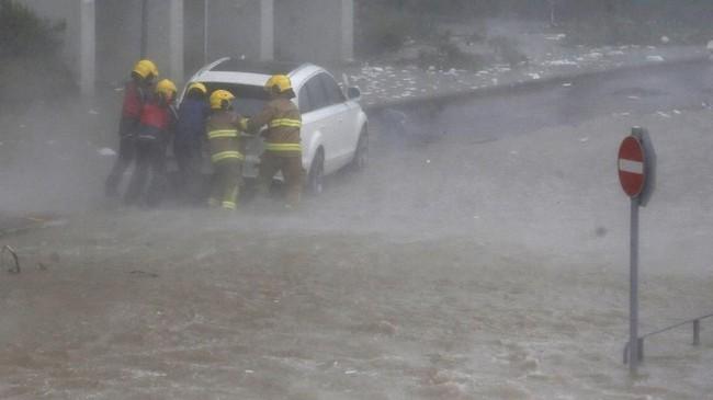 Lima orang pemadam kebakaran mendorong mobil yang mogok terkena banjir di wilayah Heng Fa Chuen, Hong Kong. (REUTERS/Bobby Yip)