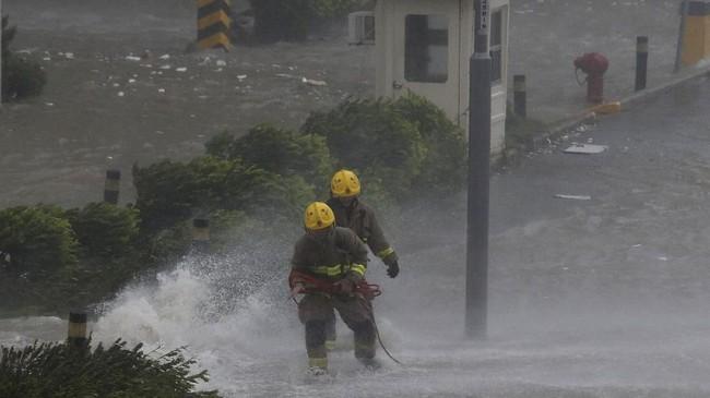 Pemadam kebakaran mencoba bertahan saat ombak tinggi menghantam pantai di Heng Fa Chuen, sebuah distrik penduduk di dekat pantai di Hong Kong. (REUTERS/Bobby Yip)