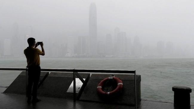 Seorang pria mengambil foto saat hujan lebat turun di Pelabuhan Victoria pada Minggu (16/9). (REUTRERS/Bobby Yip)