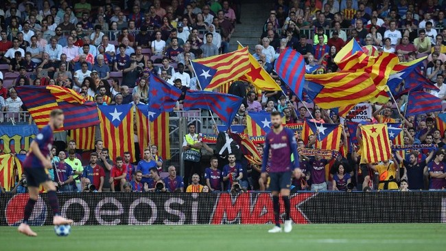 ParaBarcelona fan Barcelona mengibarkan bendera Catalonia dari tribune Stadion Camp Nou. Laga Liga Champions itu juga jadi kesempatan mereka menuntut kemerdekaan Catalonia dari Kerajaan Spanyol. (REUTERS/Albert Gea)