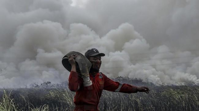 Petugas dari BPBD Kab Ogan Ilir (OI) memanggul selang air saat melakukan pemadaman kebakaran lahan di Sungai Rambutan, Indralaya Utara, Ogan Ilir (OI), Sumatera Selatan, Selasa (18/9). (ANTARA FOTO/Nova Wahyudi)
