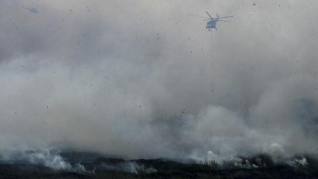 Helikopter MI-8 EY225 melakukan pemadaman kebakaran lahan dari udara (water bombing) di Desa Rambutan, Indralaya Utara, Ogan Ilir (OI), Sumatera Selatan, Senin (17/9). Luasnya lahan yang terbakar membuat petugas kesulitan untuk memadamkan kebakaran tersebut. (ANTARA FOTO/Nova Wahyudi)