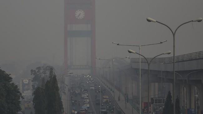 Sejumlah kendaraan melintas di atas jembatan ampera yang diselimuti kabut asap di Palembang, Sumatera Selatan, Minggu (16/9). (ANTARA FOTO/Nova Wahyudi)