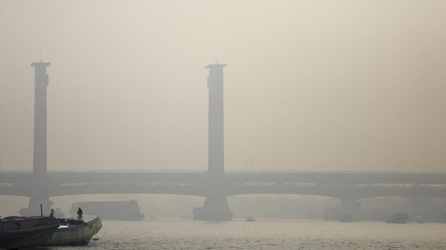 Warga beraktivitas di tepian Sungai Musi yang diselimuti kabut asap di Palembang, Sumatera Selatan, Minggu (16/9).(ANTARA FOTO/Nova Wahyudi)