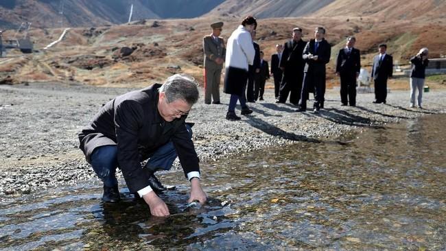 Bersama istri mereka, Kim dan Moon berjalan mengitari daerah itu dan berfoto bersama. Moon bahkan sempat mengisi botol minumnya dengan air dari danau tersebut. (Pyeongyang Press Corps/Pool via Reuters)