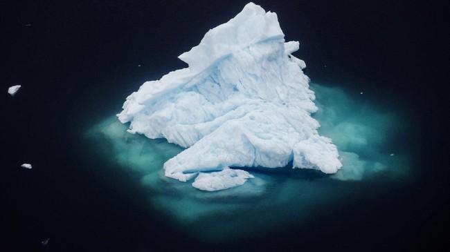 Penampakan gunung es selebar empat mil yang berasal dari pecahan Gletser Helheim saat mengapung di laut Antartika.