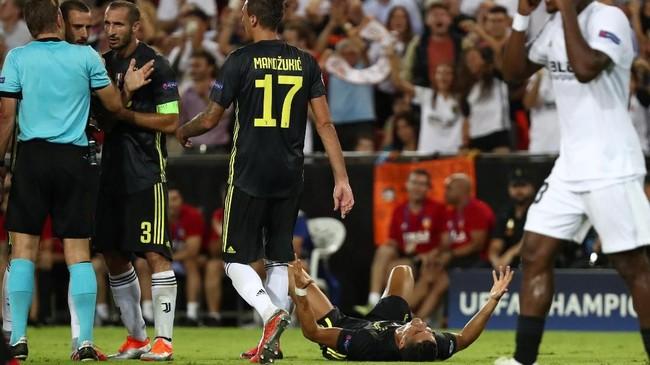Kapten Juventus Giorgio Chiellini melakukan protes ke wasit Felix Brych dengan Cristiano Ronaldo terbaring di lapangan usai mendapat kartu merah. (REUTERS/Sergio Perez)