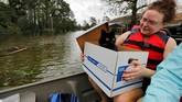 Saat melihat peliharaan yang panik, mereka langsung menghampiri, berupaya menenangkan, kemudian memasukkan peliharaan itu ke dalam perahu. (Reuters/Jonathan Drake)