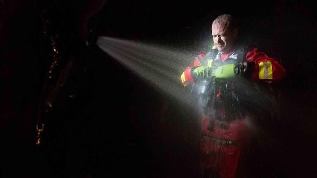 Steven Barker, seorang pemadam kebakaran di Spring Lake, disemprot air untuk menetralisir seragamnya yang digunakan dalam suatu misi penyelamatan menghadapi Badai Florence di North Carolina, Amerika Serikat. (Spc. Austin T. Boucher/U.S. Army/Handout via Reuters)