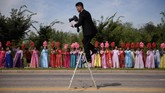 Seorang fotografer Korea Utara menaiki tangga di hadapan barisan para wanita yang mengenakan busana tradisional Korea sembari melambai-lambaikan bunga plastik di area luar kota Pyongyang. Mereka sedang menghadiri pawai internasional memperingati 70 tahun berdirinya Korut. (AFP/Ed Jones)