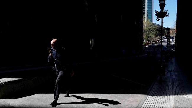 Seorang pria berbicara di telepon genggamnya sembari berjalan di kawasan bisnis di Buenos Aires, Argentina. (Reuters/Marcos Brindicci)