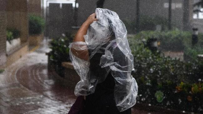Seorang pejalan kaki menggunakan ponco plastik ketika terjadinya Topan Super Mangkhut di Hong Kong. Dalam perjalanannya menuju China dari Filipina, Mangkhut sempat menewaskan 30 orang di Filipina dan menghancurkan area pertanian, juga membuat gedung-gedung tinggi bergoyang. (AFP/Anthony Wallace)