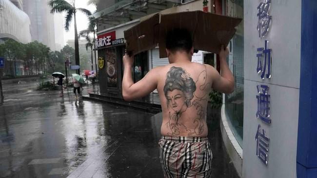 Seorang pria bertato menggunakan kertas kardus untuk melindungi diri dari hujan yang dibawa Topan Mangkhut di Provinsi Guangdong, Shenzhen, China. (Reuters/Jason Lee)