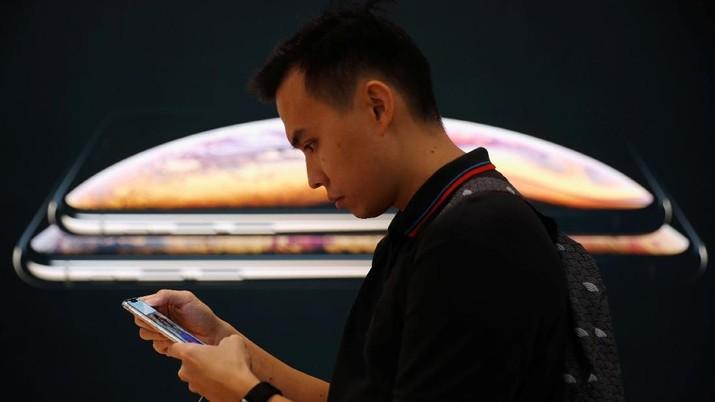 Pelanggan menggunakan iPhone di sebelah poster iPhone XS dan iPhone XS Max baru di Apple Store di Singapura 21 September 2018. REUTERS / Edgar Su