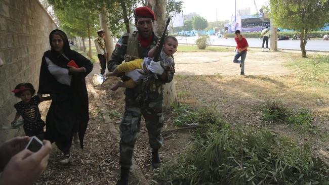 Suasana seketika kacau balau. Para tentara merangkak sembari mencari sumber tembakan, sementara perempuan dan anak-anak berlarian menyelamatkan diri mereka. (AFP Photo/Mehdi Pedramkhou)