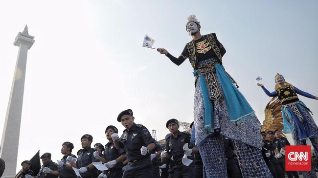 Peserta pawai dari parpol Nasdem mengikuti deklrasi kampanye damai di Monas , Jakarta, Minggu (23/9). (CNN Indonesia/Hesti Rika)