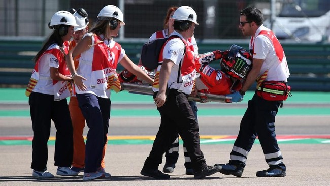 Jorge Lorenzo dibawa tim medis usai mengalami kecelakaan di MotoGP Aragon. Lorenzo menuntut Marc Marquez meminta maaf atas insiden di tikungan pertama. (REUTERS/Heino Kalis)