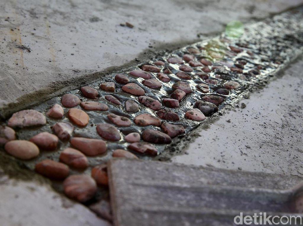 Batu kerikil tersebut ditempelkan menggunakan semen.