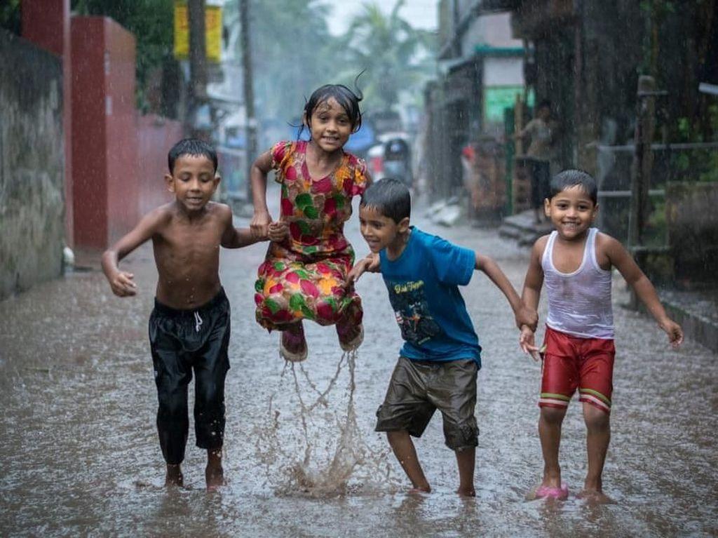 Happiness on a Rainy Day oleh fotografer Bangladesh, Fardin Oyan. Memperlihatkan anak kecil di Bangladesh bergembira meski di tengah hujan dan terancam banjir. Foto: Environmental Photographer Of The Year