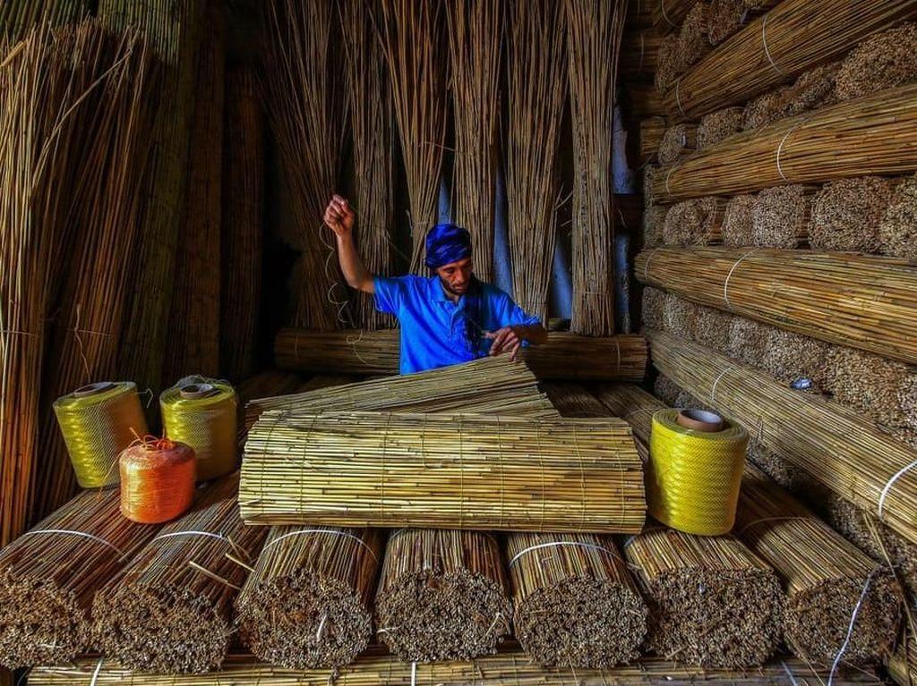 Bulrush oleh fotografer Turki, Ummu Kandilcioglu, jadi jawara di kategori keberlanjutan lingkungan. Memperlihatkan seorang pekerja membuat semacam tirai dari jerami. Foto: Environmental Photographer Of The Year