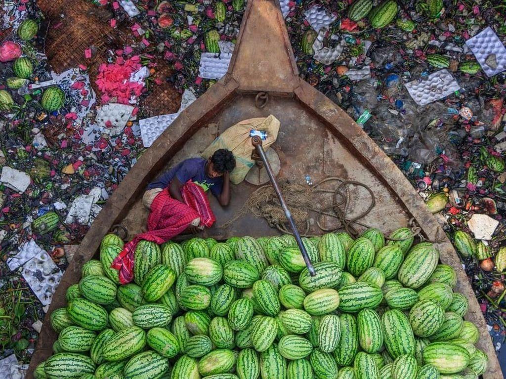 Floating Life on River Under Pollution oleh fotografer Tapan Karmaker ikut dalam deretan foto terbarik. Memperlihatkan pedagang semangka istirahat di kapalnya di tengah sungai Burigongga di Bangladesh yang penuh polusi. Foto: Environmental Photographer Of The Year