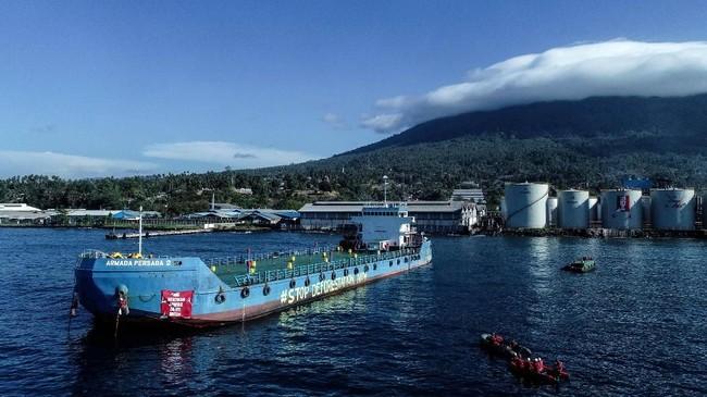 Aktivits Greenpeace melukis 'Stop Deforestasi Sekarang'pada tangki minyak sawit milikWilmar International in Bitung, Sulawesi Selatan. (Greenpeace/Nugroho Adi Putera).