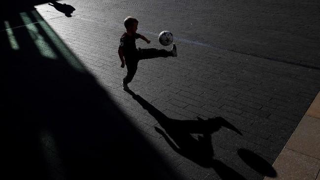 Jelang penghargaan Pemain Terbaik Dunia FIFA, seorang bocah bermain sepak bola di luar Royal Festival Hall di London. (AFP PHOTO / Adrian DENNIS)