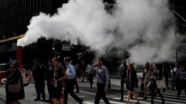 Kabut panas terlihat di udara ketika orang-orang menyebrang di jalanan Manhattan, New York, Amerika Serikat. (REUTERS/Carlos Barria)
