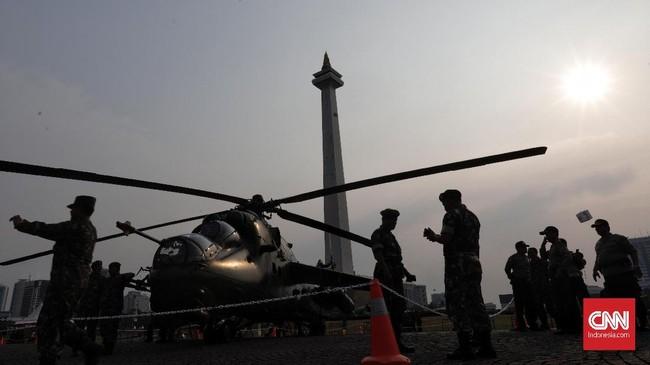Anggota TNI berjaga di depan Helikopter saat pameran Alat Utama Sistem Persenjataan di Monumen Nasional, Jakarta, Kamis (27/9). (CNN Indonesia/Adhi Wicaksono)
