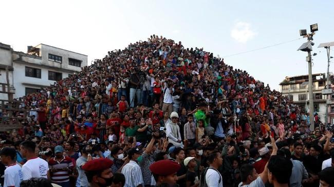 Orang-orang berkumpul untuk mengamati festival Indra Jatra di Kathmandu, Nepal. Festival tahunan yang dinamai dari dewa hujan dan nirwana ini dirayakan dengan beribadah, perayaan, bernyanyi dan menari di Lembah Kathmandu. (REUTERS/Navesh Chitrakar)